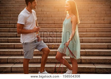 Young couple talking while standing on the stairs with dogs on leash outdoors