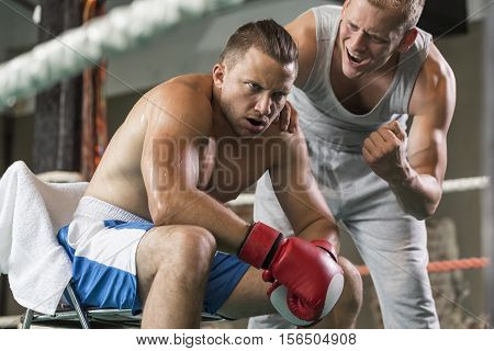 Athletic Coach Motivating Tired Boxer