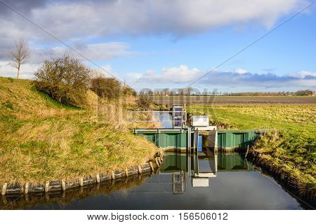 Small adjustable weir in a stream with a mirror smooth reflecting water surface in a polder in the Netherlands. It's a sunny day in the end of the winter season.