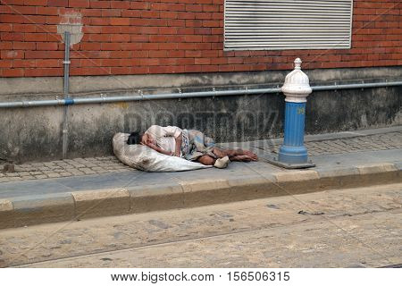 KOLKATA, INDIA - FEBRUARY 10: A homeless man lies asleep on the pavement outside the busy train station in Kolkata, India on February 10, 2016.