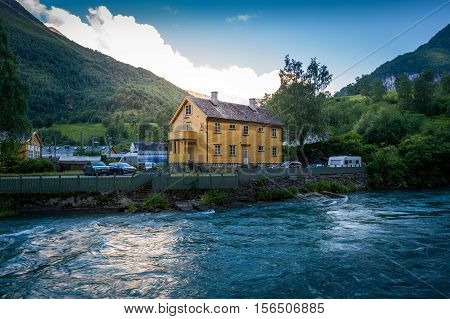 Night view of Flam mountain river and old town house. Flam, Norway.