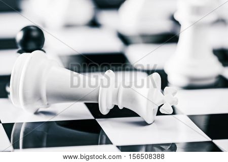 Moment of a chess game. White king laying on the foreground. Concept of defeat