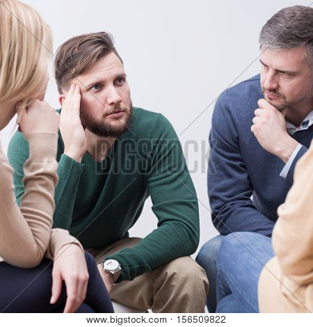 Troubled young man confiding to his supporting psychotherapy group