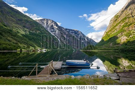 Scenic norwegian fjord landscape with wooden boats at small pier. Neroy fjord, Norway