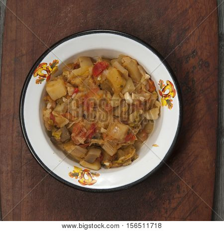 Boiled vegetables in a bowl on a timber board
