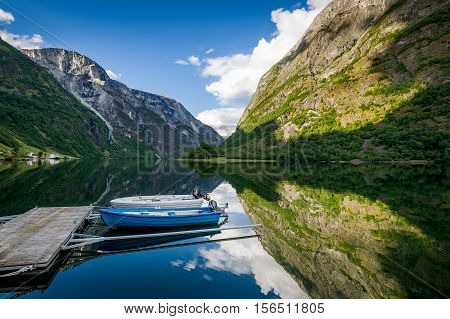 Wooden boats at scenic fjord landscape with mountains reflection on the water. Neroy fjord, Norway.