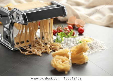 Making tagliatelle with pasta machine on kitchen table