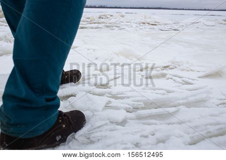 A Man Comes On The Weak Bad River. Ice Concept danger falling through the ice.