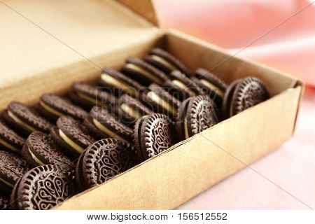 Carton box with tasty chocolate cookies on light surface