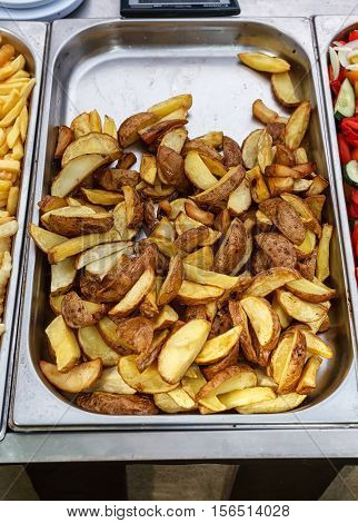 Steel container with roasted potato wedges, village style potatoes