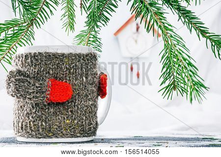 Mug in wool warmer under evergreen branches with toy cuckoo clock on the background