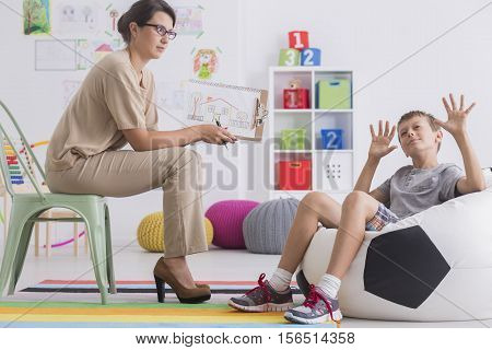 Misbehaving Child Sitting On A Modern Pouf