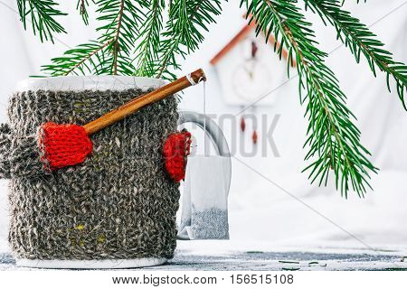 Mug in wool warmer under evergreen branches holding fishing rod with tea bag