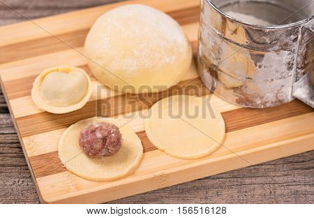 Crude dough with raw pelmeni on the chopping board over wooden background
