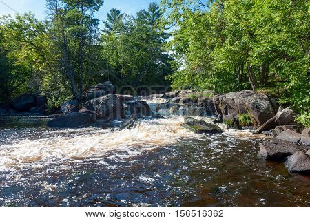 Strong Falls on the Peshtigo river in the bright rays of the autumn sun, Marinette County, Wisconsin, USA