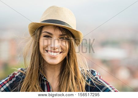 Closeup selfie portrait of beautiful young blonde casual Caucasian woman smiling, posing outdoors, wearing plaid shirt and brown fedora hat. No retouch, natural light. poster