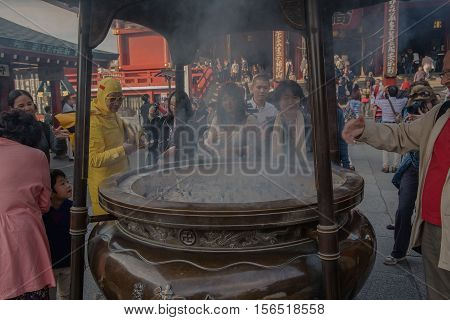 TOKYO, SENSOJI TEMPLE, JAPAN - OCTOBER 12 ,2016: Tourists put incense sticks  in Giant incense burner  in in Senso-ji Buddhist Temple in Asakusa , Tokyo, Japan. October 12 2016