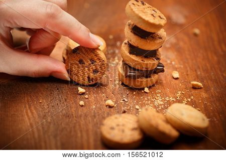 Elegant female hand holds small bisqiut with cookies and chocolate pieces turret near at wooden table background with chips scattered around. Shallow dof. Focus on hand with cookie.