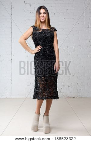 Full body woman in black dress-light background. Girl smiling striding forward hand on hip looking at the camera
