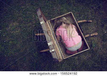 Child blond girl inside a suitcase on green grass lawn. Concept image of refugee orphan or poor child.