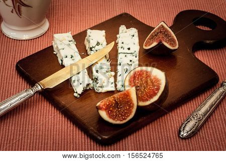 Wooden serving board with blue cheese and fresh figs.