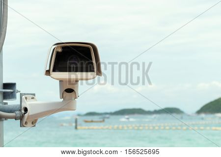 closed-circuit camera ( cctv ) security with blurry background view of sea and hill .