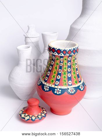 Angled view of pink Egyptian decorated handmade colorful pottery vase (arabic: Kolla) on background of white vases