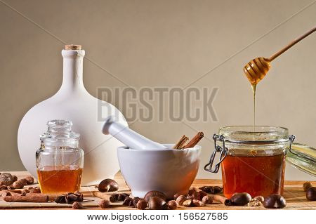 Different kinds of nuts and honey on wooden table
