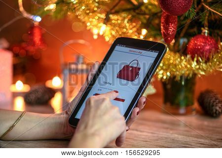 Woman makes Christmas shopping via smartphone in the online e-store