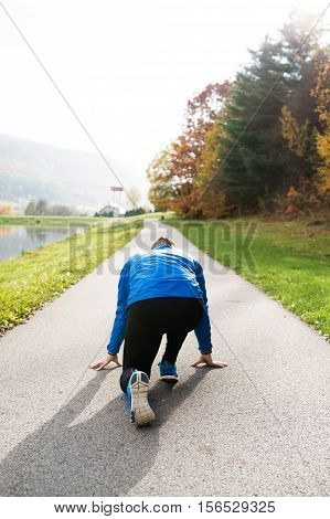 Young runner in blue jacket at the lake on an asphalt path leading through green grass in steady position. Trail runner training for cross country running outside in colorful sunny autumn nature. Rear view.