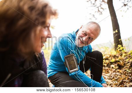Senior runners in nature, tying shoelaces. Man with smart phone and earphones. Listening music or using a fitness app. Using phone app for tracking weight loss progress, running goal or summary of his run.