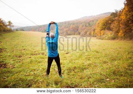 Senior runner in sunny autumn nature doing stretching. Man with smart phone in armband on his arm. Rear view.