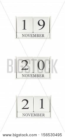 Closeup group of white wooden calendar with black 19 20 21 november word three date calendar isolated on white background