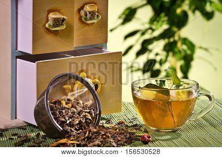 Tea Strainer and cupboard with cup on wooden table