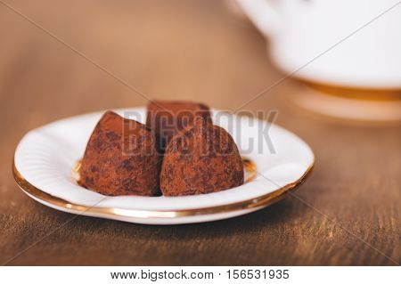 Three candies of truffle on the white plate that stand on a wooden table. On a background there is a cup. Selective focus on a forward part of candies.