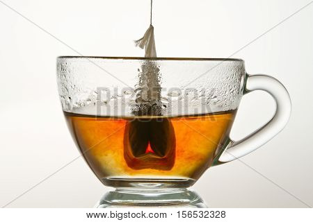 Teabag In A Cup Filled With Hot Water Isolated On White Background