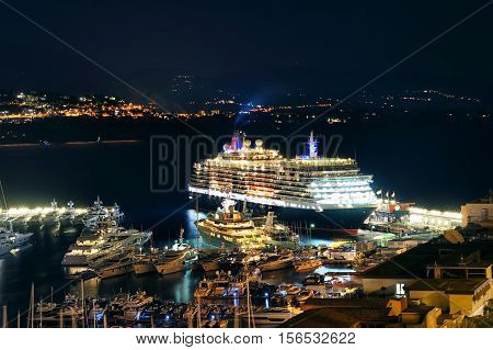 View of night city port harbor with many yachts and beautiful white giant luxury cruise ship liner on stay at terminal in Europe.
