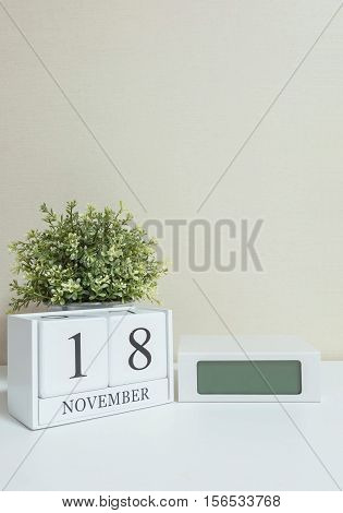 White wooden calendar with black 18 november word with clock and plant on white wood desk and cream wallpaper textured background selective focus at the calendar