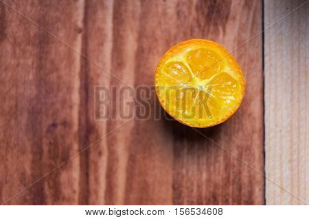 Macro image background of a slice kumquat. One piece lies on a wooden table.