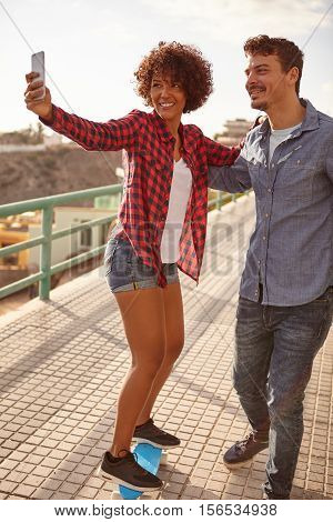 Young Couple Taking A Selfie On A Skateboard