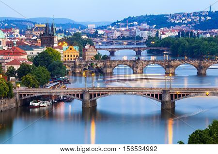 Panorama of the old part of Prague from the Letna park at dusk. Beautiful view on the bridges over the river Vltava at sunset. Old Town architecture, Czech Republic.