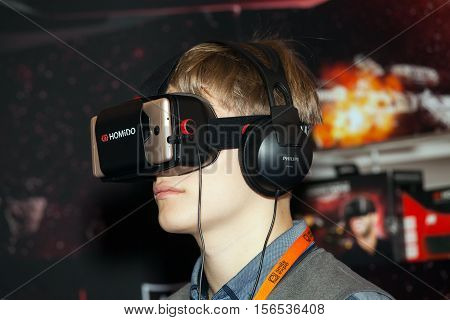 Moscow, Russia - November, 2016: Man playing with Homido virtual reality headset on Robotics Expo in Moscow, Russia