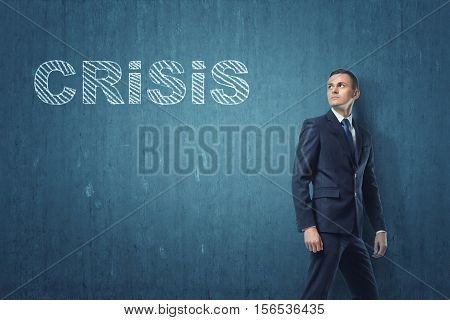 A businessman going away and turning around to look at the word 'crisis' written on the dark blue wall. Issues in business management and economics. Resolving the problems. Difficulties related to industry and enterprise.