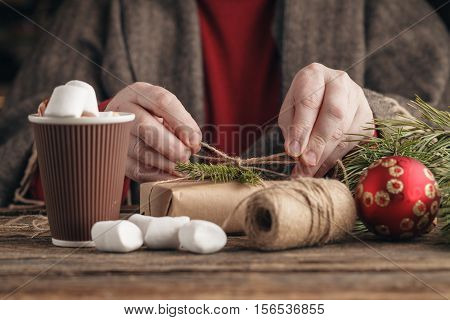 Handsome man packing xmas gifts on rustic table
