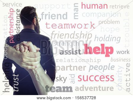 Concept depicting help. Image created using multiple exposures and adding meaningful words. Image silhouette of a man in a business suit and a handshake.