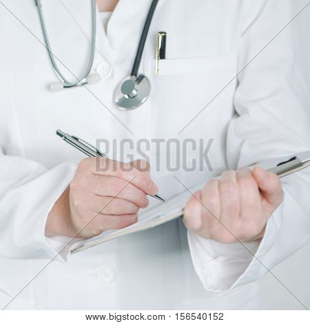Female doctor writing on clipboard notepad blank paper medical advice warning recommendation or suggestion.