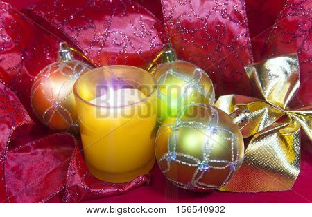 New Year's composition on a red background - ball and ribbon and a candle