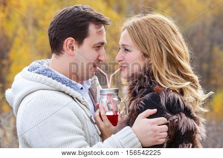 Happy young couple drinking red tea from the same pot