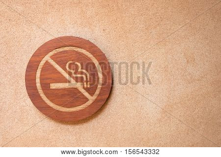 No smoking sign are made of wood on the wall.