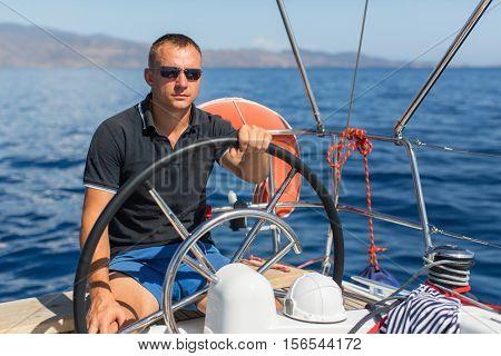 Man skipper steers boat sailing yacht on the Sea.